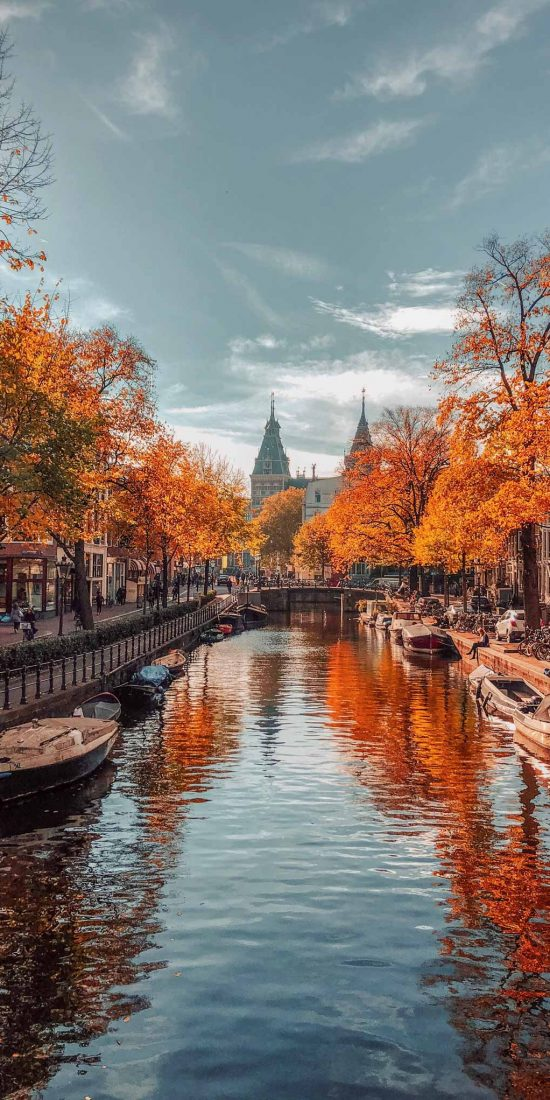 A river passing through the city of Amsterdam during autumn.