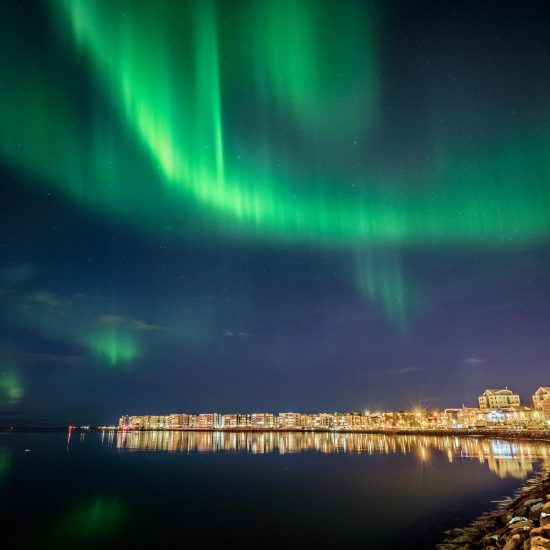 Aurora borealis Northern Lights over the city of Reykjavik, Iceland.