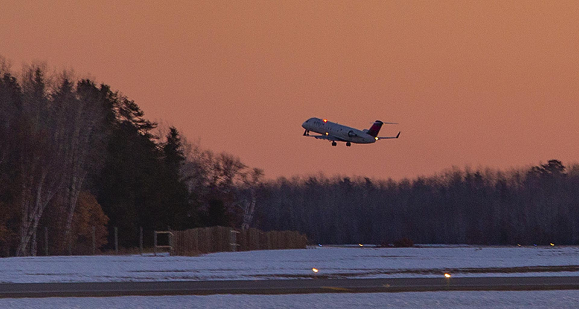 Delta jet taking off against a winter sky at dusk.